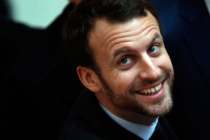 French Economy Minister Emmanuel Macron smiles as he visits a shopping center on the first day of the winter sales in Paris, Wednesday, Jan. 6, 2016. The five-week 2016 winter sales start everywhere across France on Wednesday jan.6 and end on Feb. 16. (AP Photo/Christophe Ena)