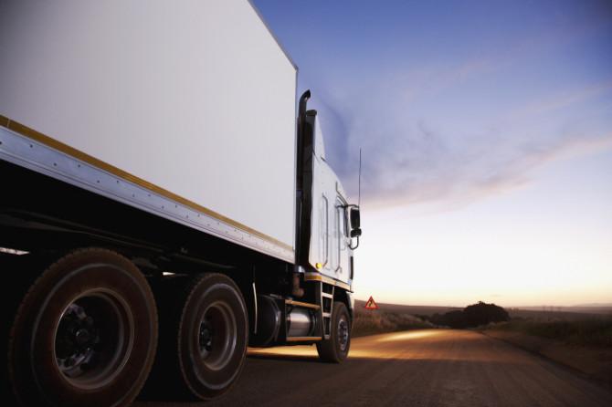 Semi-truck driving on dirt road